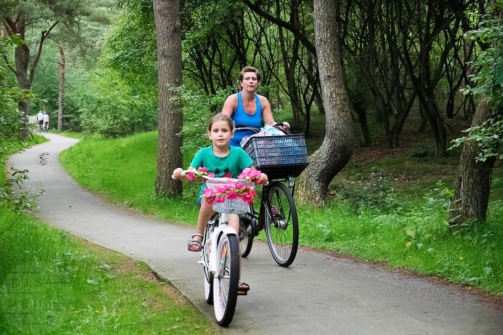 In Soest rijdt een vrouw met haar dochter op de fiets door de bossen.<br /> <br /> In Soest a woman is cycling with her daughter in the forest.