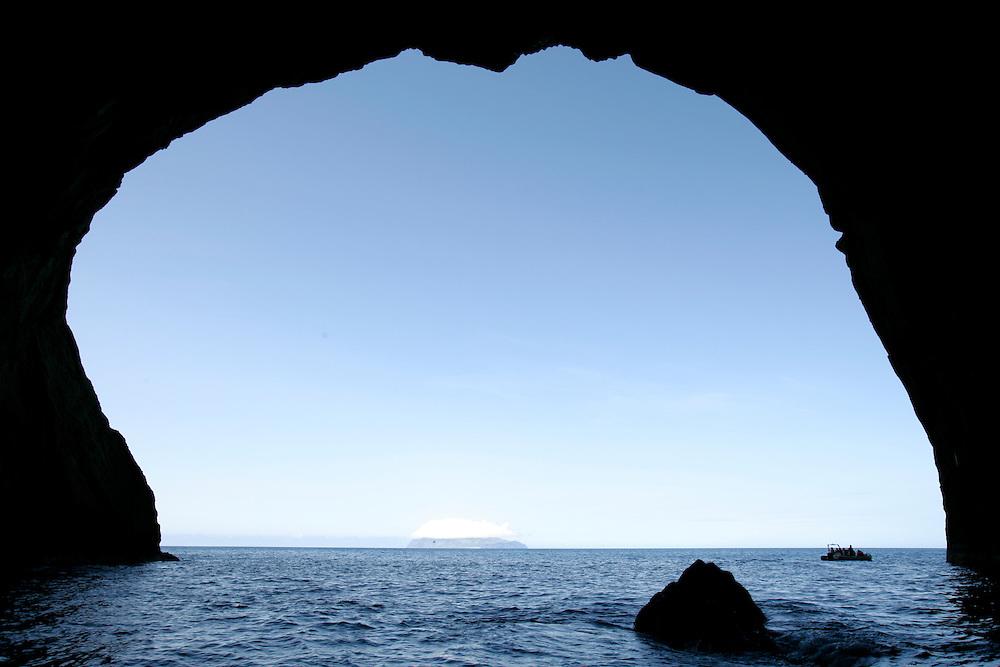 Tourists exploring sea caves in Flores island coastline.