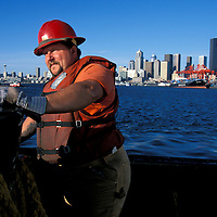 USA, Washington, Seattle, (MR) Mark Hall's works on deck of Crowley tugboat in Elliot Bay on autumn afternoon