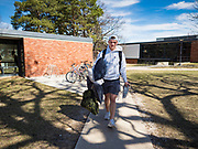 "13 MARCH 2020 - DES MOINES, IOWA: GAGE VANDERLEER, a first year student at Drake University, walks out to his car before going home for spring break. The Governor of Iowa announced Friday that 17 people in Iowa have tested positive for the Novel Coronavirus. Of those, 15 people were exposed on the same cruise in Egypt, the others were exposed through travel but were not on the same cruise. The Governor said there has not yet been any ""community spread"" in Iowa. All of the Iowans who have tested positive are in self quarantine. Across Iowa, municipalities and businesses are taking steps to implement ""social distancing."" Most of the colleges in Iowa, including Drake University, have announced that they will remain closed after their spring breaks and that classes will move to online only, after spring break. Many businesses in Des Moines, including Nationwide Insurance and EMC Insurance, have announced plans to have their employees to telecommute. The mayor of Des Moines has urged event planners to consider canceling large events.     PHOTO BY JACK KURTZ"