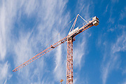 Construction crane with a blue sky and light white clouds background