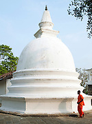 Young monk walking around a Buddhist temple dome at the Mulkirigala Monastery, Sri Lanka