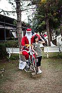 A vietnamese woman poses in front of a fake Santa Claus, Cock Church, Da Lat, Vietnam, Southeast Asia