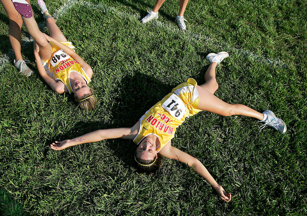 Lexie Rael, right, and Shea Smalley, left, both from Marion High School, stretch before the varsity girls race at the Prairie Invitational cross country meet at Prairie High School in Cedar Rapids on Tuesday, September 1, 2009. (Crystal LoGiudice/The Gazette).