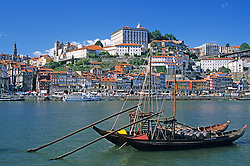 EU, Portugal, Porto (Oporto). Historic port wine barges (barcos rabelos) moored in Douro River with the Ribeira District in the background.