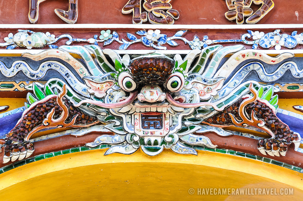 A brightly colored sculpted dragon at the Imperial City in Hue, Vietnam. A self-enclosed and fortified palace, the complex includes the Purple Forbidden City, which was the inner sanctum of the imperial household, as well as temples, courtyards, gardens, and other buildings. Much of the Imperial City was damaged or destroyed during the Vietnam War. It is now designated as a UNESCO World Heritage site.