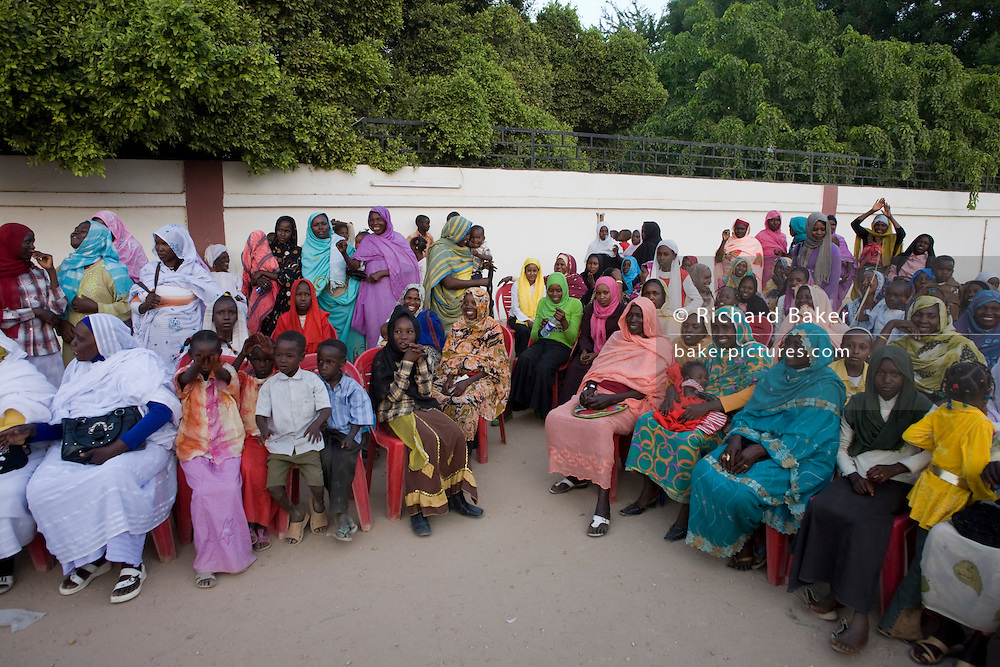 Some ladies attending the first-ever international Conference on Womens' Challenge in Darfur, raise their hands in the hope of peace while gathering to hear speeches by the British peer Lord Ahmed and traditional songs by local singers just outside the compound walls belonging to the Govenor of North Darfur in Al Fasher (also spelled, Al-Fashir) where the women from remote parts of Sudan gathered to discuss peace and political issues and celebrate Darfurian culture.