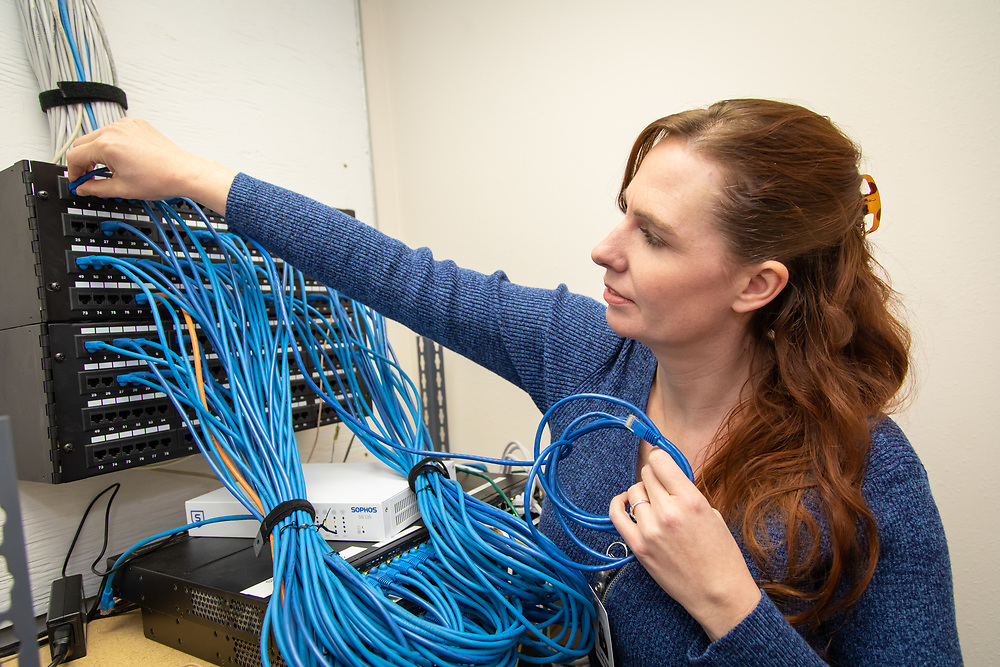 Leia Roth, IT manager, configures networking cables at the Custer County Medical Center.