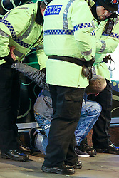 © Licensed to London News Pictures . 01/01/2014 . Manchester , UK . Police detain a man on the ground outside the Birdcage in central Manchester . Revellers see in the New Year in Manchester today (January 1st 2014) as police report that officers are at full stretch responding to calls . Photo credit : Joel Goodman/LNP