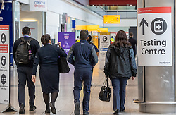 "© Licensed to London News Pictures. 09/04/2021. London, UK. Members of the public walk past a test centre sign at London Heathrow. Today, Transport Secretary Grant Shapps sets out details of the government's ""traffic Light"" system for May 17th so that the public can travel abroad with passengers requiring to take a private covid-19 test each way, costing as much as £150.00 for one test. Photo credit: Alex Lentati/LNP"