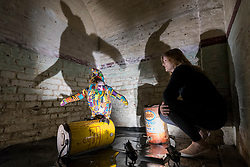 """© Licensed to London News Pictures. 24/05/2018. LONDON, UK. London, UK.  24 May 2018. An assistant views an animatronic South African penguin at the preview of """"Missing"""" an exhibition by artist and environmentalist Louis Masai at the Crypt Gallery in Euston.  The exhibition features sculptures, installations and paintings depicting 20 endangered species across the world from the South African penguin to the humble bumble bee.  The show runs 25 to 27 May 2018. Photo credit: Stephen Chung/LNP"""