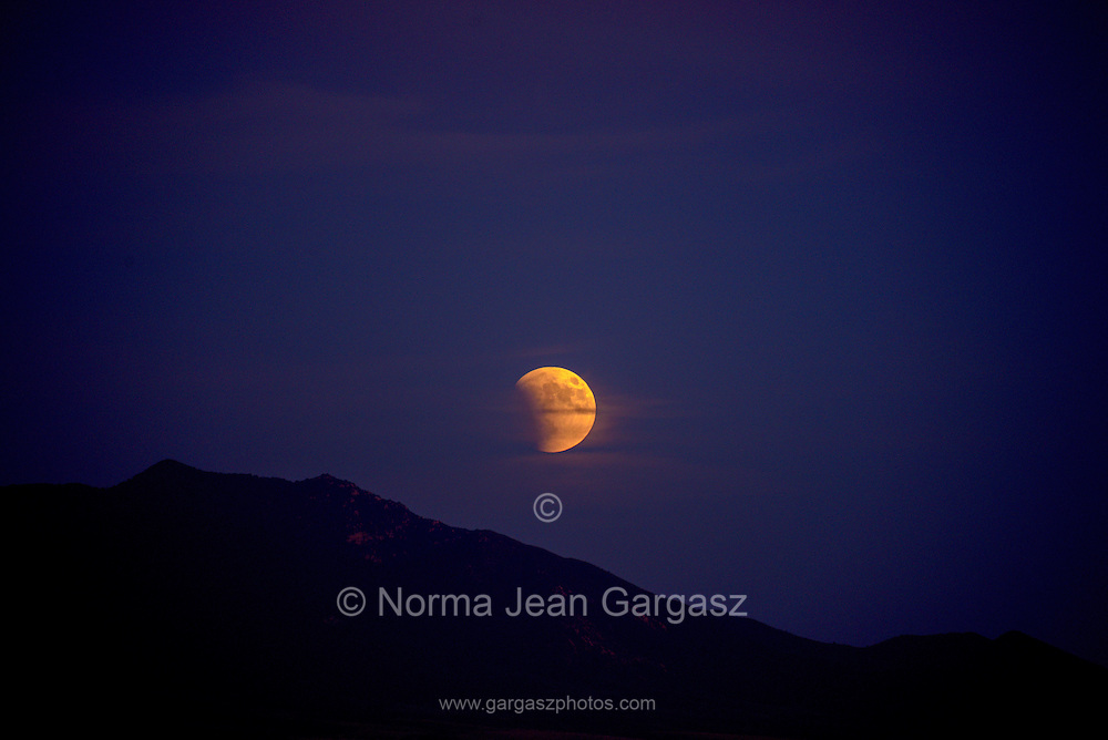 A total lunar eclipse in progress rises over the Whetstone Mountains north of Sonoita, Arizona, USA, on September 27, 2015.