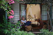 Young Woman relaxing on the Verandah of a B&B, Maitland, Australia
