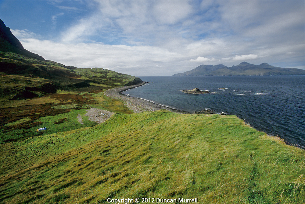 """After the unforgettable rigours of my crossing from Ardnamurchan to Muck, the relatively short passage to the next island of the Small Isles, Eigg, was relatively comfortable. It is the second largest of the four islands with an area of 31 km2 (12 sq mi), 9 km (5.6 mi) long from north to south, and 5 km (3.1 mi), with a population of about 50. The main settlement on Eigg is Cleasdale, a fertile coastal plain in the north west. It is known for its quartz beach, called the """"singing sands"""" because of the squeaking noise it makes if walked on when dry. The centre of the island is a moorland plateau, rising to 393 metres (1,289 ft) at An Sgurr, a dramatic stump of pitchstone, sheer on three sides.<br /> I landed on the south of the island on a beach near the ferry jetty at Galmisdale where there is a sheltered anchorage for boats, and a new building near the jetty, housing the post office, shop, craft shop, café, restaurant and bar, and of great benefit to me, toilet and shower facilities that are open 24 hrs a day. This modern and welcoming building near the ferry jetty gives a good indication of how important tourism is to the local economy of Eigg, especially during the summer months, and it was a welcome haven for me whenever I was in need of some extra treats during the time that I was camping on the island. At first I camped behind the beach in Galmisdale Bay, and then I paddled around the rugged and steep east coast to find a place to camp with more solitude."""
