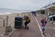 A woman tugs at the plastic bin bag on the seafront at St Leonards, on 3rd May 2021, in St Leonards, Sussex, England.