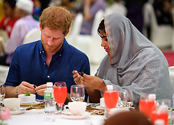 Prince Harry sits down for iftar, breaking of the fast during Ramadan at the Jamiyah Education Centre in Singapore.