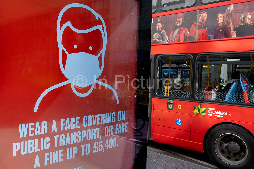 A London bus carrying ads for a TV channel drives past a government ad, warning of fines if passengers do not wear face coverings during the third lockdown of the Coronavirus pandemic, on 29th March 2021, in London, England.