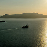Santorini. Cyclades. Greece. View of a lone boat sailing the shimmering golden sun lit water of the caldera.