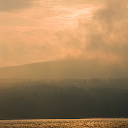 The sun burns through the fog at Lake Sunapee State Beach in Newbury, New Hampshire.