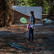 A young refugee from Aleppo, Syria holds her Eid Al Fitr balloon and gift bag distributed by an INGO in Ritsona refugee camp, an hour north of Athens, Greece. July 2016.<br /> <br /> The Balkan borders were closed to refugees in March 2016. According to the IRC, as of April 2017 62,000 refugees are stranded in Greece, waiting to be relocated to a welcoming country.