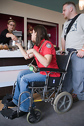 Young woman with cerebral palsy in a wheelchair with her boyfriend; paying at the counter of a café,