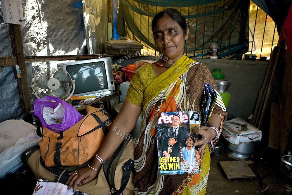 Shammi Bi, 36, the mother of Azharuddin Ismail, 10, the child actor playing the role of 'young Salim', the brother of Jamal, protagonist of Slumdog Millionaire, the famous movie winner of 8 Oscar Academy Awards in December 2008, is showing the cover of People Magazine with a picture of his child, the director Danny Boyle and the other child actor from Mumbai's slums, Rubina Ali, in her home next to the train station of Bandra (East), Mumbai, India. Various promises were made to lift the two young actors (Azharuddin Ismail and Rubina Ali) from poverty and slum-life but as of the end of May 2009 anything is yet to happen. Rubina's house was recently demolished with no notice as it lay on land owned by the Maharashtra train authorities and she is now permanently living with her uncle's family in a home a stone-throw away in the same slum. Azharuddin's home too was demolished in the past two weeks, as it happens every year in his case, because the concrete walls were preventing local authorities to clear a drain passing right behind it. As usual, his father is looking into restoring the walls as soon as the work on the drain has been completed.