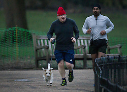 © Licensed to London News Pictures. 22/02/2021. London, UK. Prime Minister Boris Johnson runs with his dog Dilyn and a close protection officer in Westminster. Later Mr Johnson is expected to announce his roadmap to easing the lockdown as Covid-19 infection and death rates continue to decline. Photo credit: Peter Macdiarmid/LNP