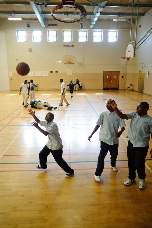 (photo by Matt Roth).Friday, May 14, 2010..Baltimore Freedom Academy eight-graders (clockwise from left) Treymane Jones, Quashawn Tate, and Willard Brewington, play under a tattered, practically useless, net during their gym class Friday, May 14, 2010. In the background, two boys go to the floor over possession of a basketball in a separate game. Students play in their school clothes, rather than gym garb, because the boys locker has been declared hazardous for student use. ..The building housing the Baltimore Freedom Academy, a grade 6-12 Baltimore public charter school focusing in social justice, was built in 1960. Fifty years later, the school is in disrepair. Old pipes make water from the fountains undrinkable. Asbestos makes repairing/replacing the pipes a hazard. The school has no air conditioning which makes the year-round school unbearable in the summer. The most derelict area is the boys locker room, where students are not allowed.