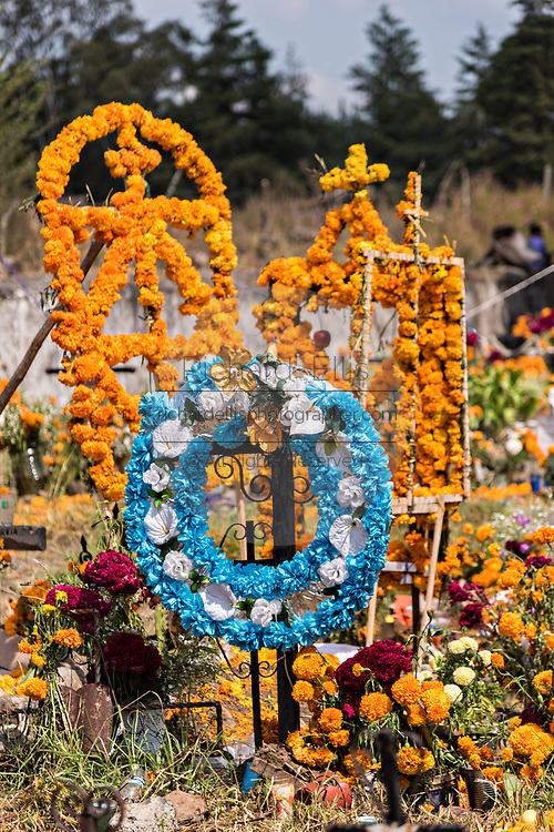 Wreaths and marigold altars decorate tombs during the Day of the Dead festival November 2, 2017 in Ihuatzio, Michoacan, Mexico.  The festival has been celebrated since the Aztec empire celebrates ancestors and deceased loved ones.