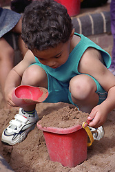 Nursery school boy playing with bucket full of sand and spade in playground sandpit,
