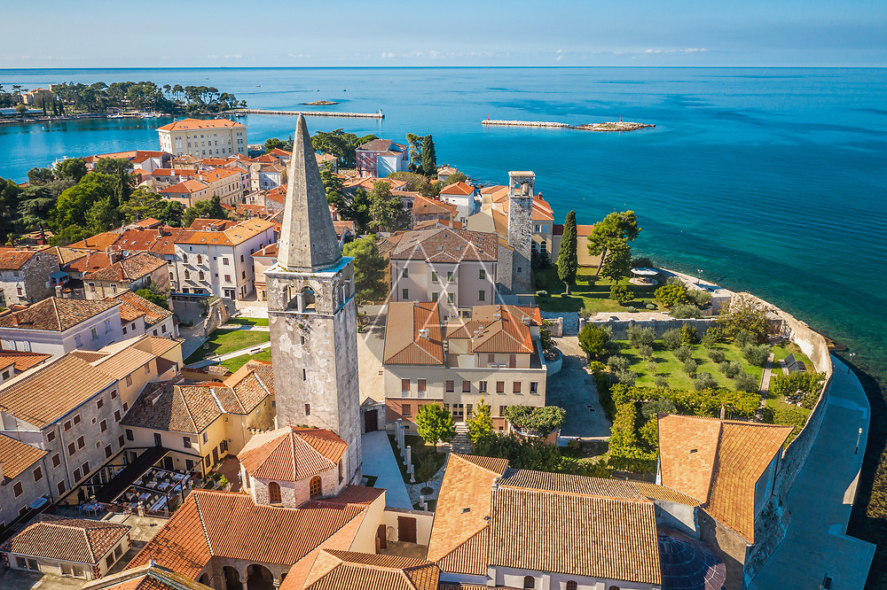 Aerial view of the Euphrasic Basilica surrounded by turquoise water in Porec, Croatia