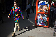 A woman pedestrian strides past a red phone kiosk advertising Natwest's online banking aimed at new University students. In bright sunshine, the phone box carries the ad of a woman sipping from a mug - the typical student up late - while checking her balance via smartphone as the woman paces past in a chequered top, almost the same pattern as on the student's cup.