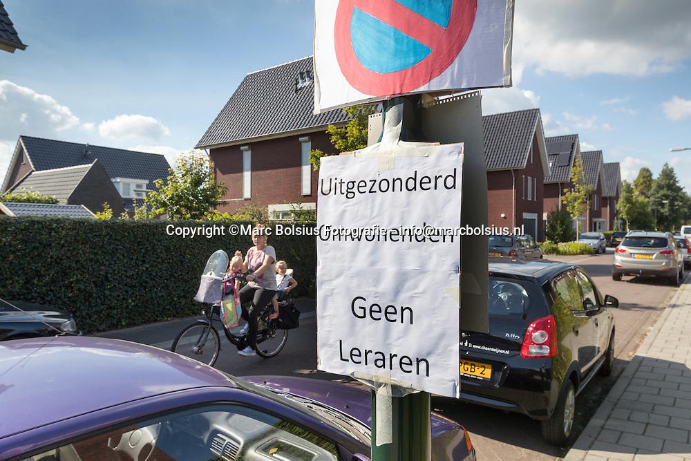 Nederland,  Schijndel, bewoners in de buurt van het Eldecollege op de Putsteeg zijn de parkeeroverlast beu ijn hun buurt en demomstreren met spandoeken.