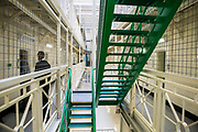 A prisoner is escorted to his cell by an officer next to the stairs on Benbow wing inside HMP/YOI Portland, a resettlement prison with a capacity for 530 prisoners. Dorset, United Kingdom.