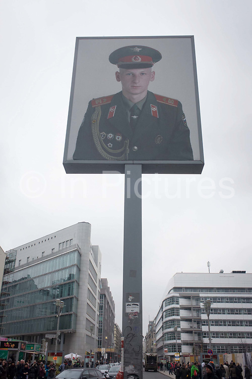 """The portrait of a Soviet soldier sits high above modern Friedrishstrasse in modern Berlin at the location of  the former Checkpoint Charlie, the former border between Communist East and West Berlin during the Cold War. The Berlin Wall was a barrier constructed by the German Democratic Republic (GDR, East Germany) starting on 13 August 1961, that completely cut off (by land) West Berlin from surrounding East Germany and from East Berlin. The Eastern Bloc claimed that the wall was erected to protect its population from fascist elements conspiring to prevent the """"will of the people"""" in building a socialist state in East Germany. In practice, the Wall served to prevent the massive emigration and defection that marked Germany and the communist Eastern Bloc during the post-World War II period."""