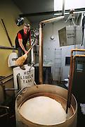 Buffalo Bill's Brewery, founded by photographer Bill Owens in 1983. In Hayward, California. Bill Owens shovels grain into a fermentation tank. MODEL RELEASED.
