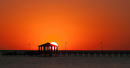 The Biloxi Lighthouse pier and the first sunset of in the New Year. Photo shot in Biloxi, Mississippi MS along the Mississippi Gulf Coast.