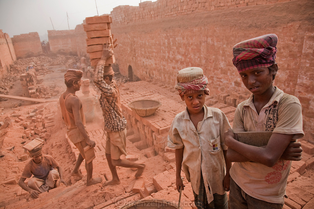 Child workers take a break at the JRB brick factory near Sonargaon, outside Dhaka, Bangladesh. Unlike the garment industry, where child labor restrictions are more closely monitored, rural agriculture and industry are less regulated and there is little if any oversight or enforcement. When queried, some laborers at a nearby site defended the use of child workers, saying poor families need their children to be breadwinners now if they are to have any kind of future. The heavy clay soils along the river near the market town of Sonargaon are well suited for making bricks. At the JRB brick factory, workers of all ages move raw bricks from long, stacked rows, where they first dry in the sun, to the smoky coal-fired kilns.