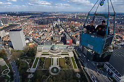 """Iron workers hang high above """"La Botanique"""" the botanical gardens, and a well known Brussels landmark, as they apply the exterior skin on a new 35 story skyscraper being built in downtown Brussels. (Photo  © Jock Fistick)"""