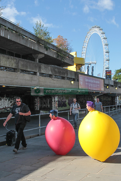 New York clown duo Acrobuffos speak to a passer-by while performing part of Air Play, which will be performed as part of Southbank Centre's Festival of Love from August 9 to 14. The duo, Seth Bloom and Christina Gelsone, will be performing displays with flying umbrellas, balloons and kites.