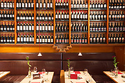 Shelves of bottles of German and other nationality red wine on display above dining tables in Miera Restaurant in Lubeck, Germany
