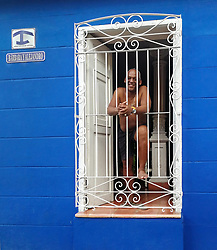 Trinidad in Cuba. Man on window in bed and breakfast. Casa particular.
