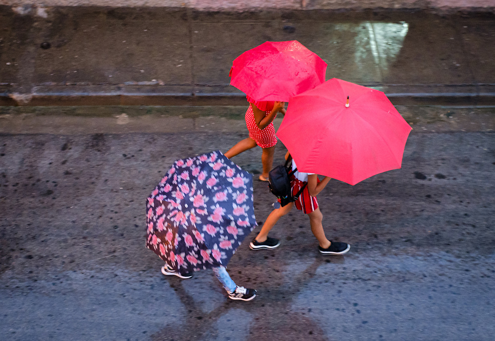 SANTIAGO DE CUBA, CUBA - CIRCA JANUARY 2020: Pedestrians walking in Santiago de Cuba during a rainy day.