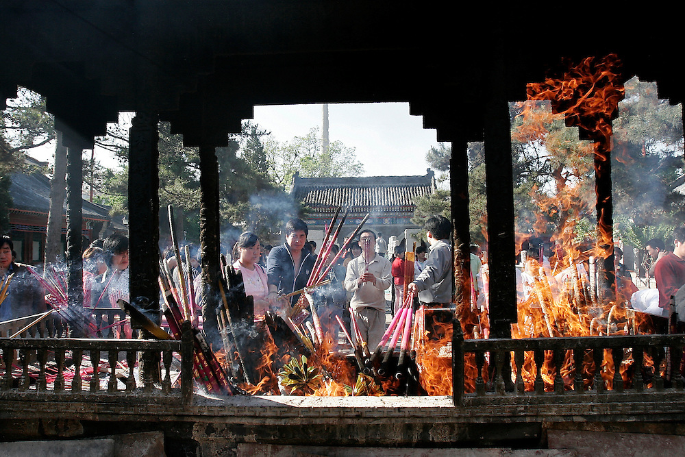 Daoists gather in front of a large burner and offer incense at Baiyuguan.  Baiyuguan,called White Cloud Temple in English, is over 1,200 years old and stands the south west of Beijing, China.  White Cloud Temple is the largest Daoist structure in Beijing and home of the Dragon Gate sect of Daoism.