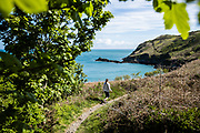 Woman taking in the views of the sea and coastline, as she walks along the North Coast cliff paths in Jersey, Channel Islands