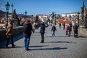 A young lady getting a portrait with birds on Charles Bridge. On March 1st, 2021 the state of emergency in the Czech Republic was reinstalled because of fast increasing numbers in infections. The lockdown was reinstated and the restriction of the free movement of people has taken effect. Currently, the country remains at the highest stage of the anti-epidemiological system and the newly imposed restriction will last at least three weeks to curb the epidemic.