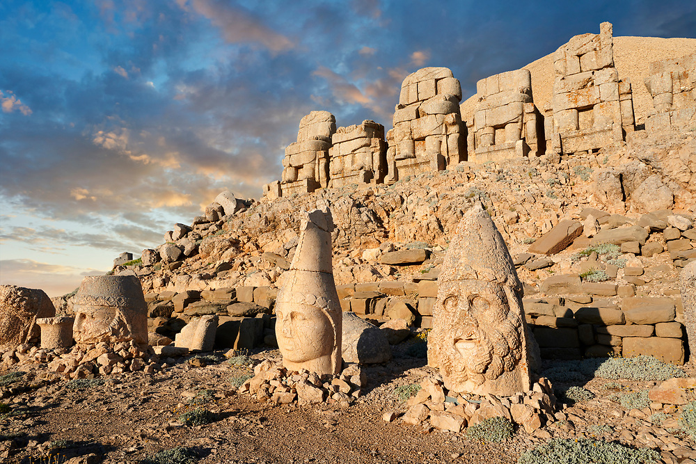 Statue heads at sunset, from right, Herekles, Apollo & Zeus, with headless seated statues in front of the stone pyramid 62 BC Royal Tomb of King Antiochus I Theos of Commagene, east Terrace, Mount Nemrut or Nemrud Dagi summit, near Adıyaman, Turkey