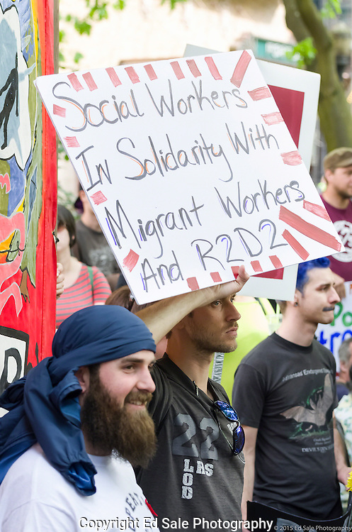 May Day 2015 demonstrators in Portland, Oregon hold sign showing social worker support for migrant workers and the homeless.