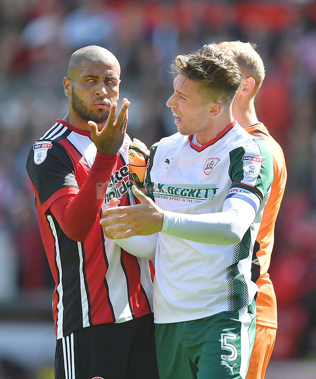 Barnsley's Angus MacDonald and Sheffield United's Leon Clarke (left) clash during the game