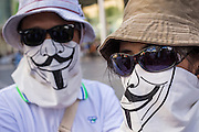 """09 JUNE 2013 - BANGKOK, THAILAND:   A White Mask protester at Central World in Bangkok Sunday. The White Mask protesters wear the Guy Fawkes mask popularized by the movie """"V for Vendetta"""" and the protest groups Anonymous and Occupy. Several hundred members of the White Mask movement gathered on the plaza in front of Central World, a large shopping complex at the Ratchaprasong Intersection in Bangkok, to protest against the government of Thai Prime Minister Yingluck Shinawatra. They say that her government is corrupt and is a """"puppet"""" of ousted (and exiled) former PM Thaksin Shinawatra. Thaksin is Yingluck's brother. She was elected in 2011 when her brother endorsed her.    PHOTO BY JACK KURTZ"""